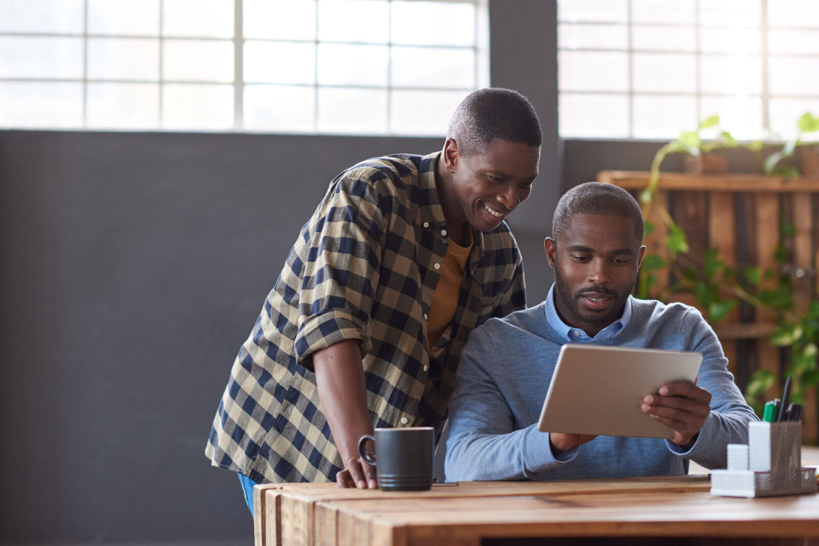 78370780 - smiling african coworkers using a digital tablet in an office